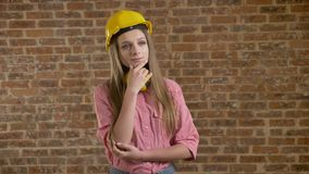 Young beautiful girl builder standing and evaluating something, thinking process, brick background.  stock video