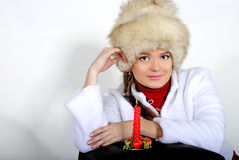 The young beautiful girl in a cap with a candlе. The young beautiful girl in a fur cap with a candle Stock Images