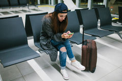 A young beautiful girl in casual style with a suitcase sits in the airport waiting room and uses a mobile phone. Night Royalty Free Stock Photography