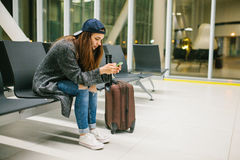A young beautiful girl in casual style with a suitcase sits in the airport waiting room and uses a mobile phone. Night Stock Image