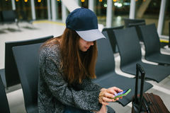 A young beautiful girl in casual style with a suitcase sits in the airport waiting room and uses a mobile phone. Night Stock Photos