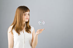 Young beautiful girl catch soap bubble Royalty Free Stock Photos