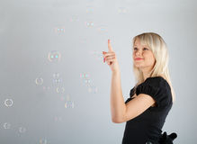 Young beautiful girl catch soap bubbles Stock Photo