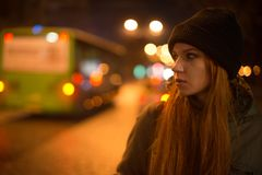 Young beautiful girl catches a taxi in the city street at night Stock Image