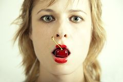 Young beautiful girl with cherry in mouth Royalty Free Stock Photos