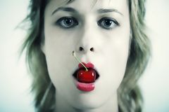 Young beautiful girl with cherry in mouth Stock Photography