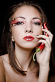 Young beautiful girl with chili pepper. Studio portrait on black royalty free stock image