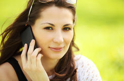 Young beautiful girl in city park speaks by mobile phon. Image of young beautiful girl in city park speaks by mobile phone Royalty Free Stock Image