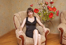 Young beautiful girl with colors. In an arm-chair Stock Image