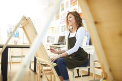 Young beautiful girl with curly hair dressed in white blouse, brown apron and jeans paints a picture at the easel in the royalty free stock photos