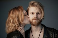 Young beautiful girl with curly hair kissing her bearded boyfriend stock images