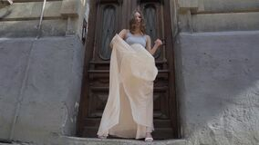 Young beautiful girl is dancing in flowing skirt in old city slow motion