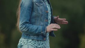 Young beautiful girl dancing in front of trees at music festival. Young beautiful caucasian girl in denim jacket dancing in front of green trees and bushesat stock video