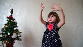 Young beautiful girl dancing next to Christmas tree. stock footage