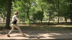 Young beautiful girl is dancing on path in park in daytime, in summer, movement concept, side view, dolly shot.  stock video