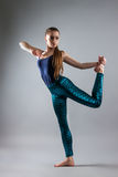 Young beautiful girl dancing. woman in a blue T-shirt and blue tights. Royalty Free Stock Photography