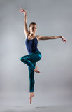 Young beautiful girl dancing. woman in a blue T-shirt and blue tights. Royalty Free Stock Photos