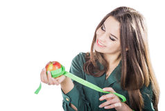 Young beautiful girl with dark hair isolated on a white background holding an apple with a tape measure.Smile. Woman hand with green apple and measure tape Royalty Free Stock Image