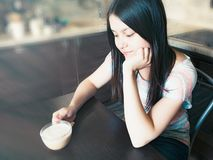 Young beautiful girl with dark long hair sits at a table with a cup of coffee and dreams about something stock images