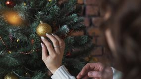 Young beautiful girl decorates the Christmas tree while her boyfriend holds a Christmas gift.