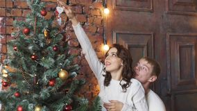 Young beautiful girl decorates the Christmas tree while her boyfriend holds a Christmas gift. Young beautiful girl decorates a Christmas tree while her stock video footage