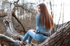 Young beautiful girl in denim jacket and jeans sits on a tree an Royalty Free Stock Photo