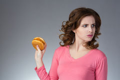 Young beautiful girl disdainfully holding a junk food from fast. Food sandwich and do not want to eat on a gray background Royalty Free Stock Photo