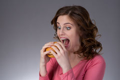 Young beautiful girl disdainfully holding a junk food from fast. Food sandwich and do not want to eat on a gray background Stock Image