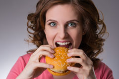 Young beautiful girl disdainfully holding a junk food from fast. Food sandwich and do not want to eat on a gray background Royalty Free Stock Photos