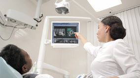 The dentist shows a picture of the x-ray on the monitor to the patient Young African American male patient at chair at. Young beautiful girl doctor dentist stock video footage