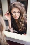 Beautiful girl does makeup Stock Photography