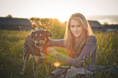 Young beautiful girl with dog sitting on the ground Royalty Free Stock Photo