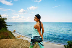 Young beautiful girl doing exercises on the beach stock photo