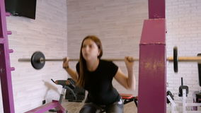 Young beautiful girl doing exercises with dumbbells at the gym. stock video footage