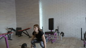 Young beautiful girl doing exercises with dumbbells at the gym. slow motion stock footage