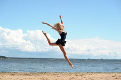 Young beautiful girl doing gymnastic jumps outdoors Stock Images