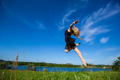 Young  girl doing gymnastic jumps outdoors Royalty Free Stock Image