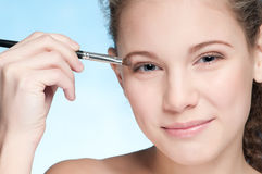 Young beautiful girl doing make-up by brush Stock Photography