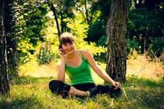Young beautiful girl doing physical exercises in a park. stock photos