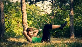 Young beautiful girl doing physical exercises in a park. stock photo