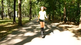 Young beautiful girl doing sports in the park. A woman jumps on special shoes for fitness. stock video footage