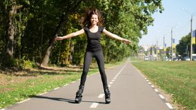 Young beautiful girl doing sports in the park. A woman jumps on special shoes for fitness. stock video