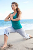 Young beautiful girl doing yoga on the beach Royalty Free Stock Image