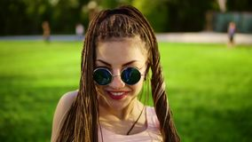 Young beautiful girl with dreads dancing in a park. Beautiful woman in jeans and sunglasses listening to music and