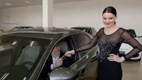 A young girl in a dress gives a man the keys to his new car in the showroom. stock video