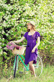 Young beautiful girl in dress and hat with long hair with flowers in basket on vintage bike. Fashioned woman. Royalty Free Stock Photos