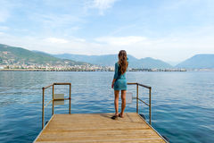 Young beautiful girl in the dress standing on pier Royalty Free Stock Photos