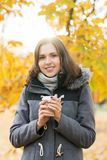 Young and beautiful girl drinking coffee in an autumn park Royalty Free Stock Photography