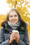 Young and beautiful girl drinking coffee in an autumn park Royalty Free Stock Images