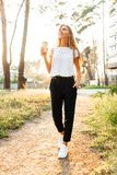Young beautiful girl drinking coffee walking around the city, in royalty free stock images